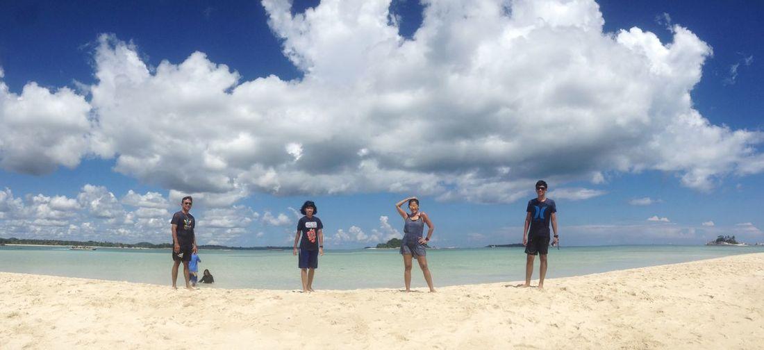 People standing on beach against blue sky