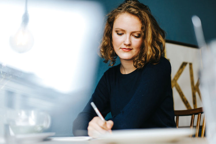Portrait of blonde woman writing