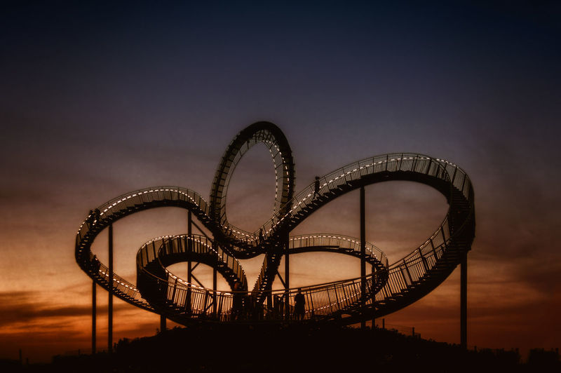 Silhouette Of Rollercoaster Against Sky During Sunset