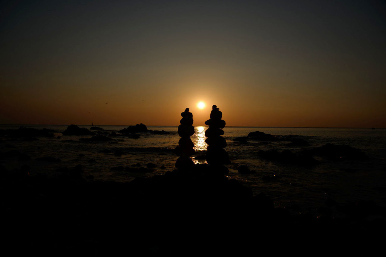 sunset, silhouette, sea, nature, scenics, beauty in nature, water, tranquility, horizon over water, tranquil scene, sky, togetherness, real people, sun, beach, outdoors, leisure activity, two people, standing, friendship, day