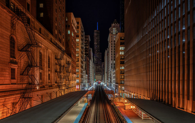 Railroad tracks amidst buildings in city at night