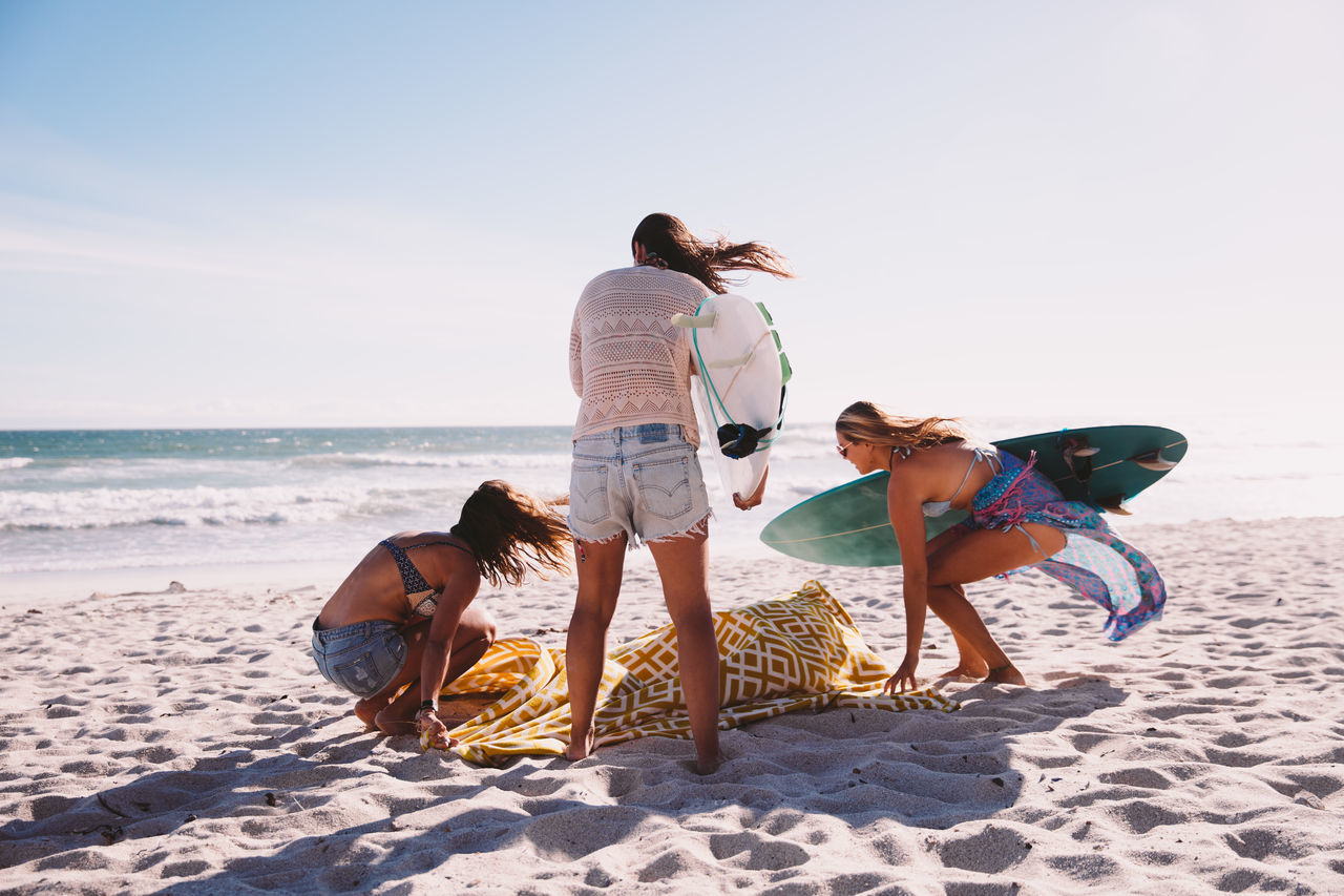 Female friends with surfboards and blanket at beach against clear sky