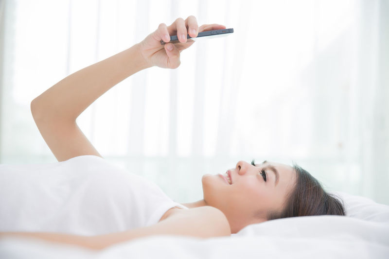 Adult Arms Raised Beautiful Woman Bed Domestic Room Focus On Foreground Furniture Headshot Human Arm Indoors  Leisure Activity Lifestyles Lying Down People Portrait Real People Relaxation White Color Women Young Adult Young Women