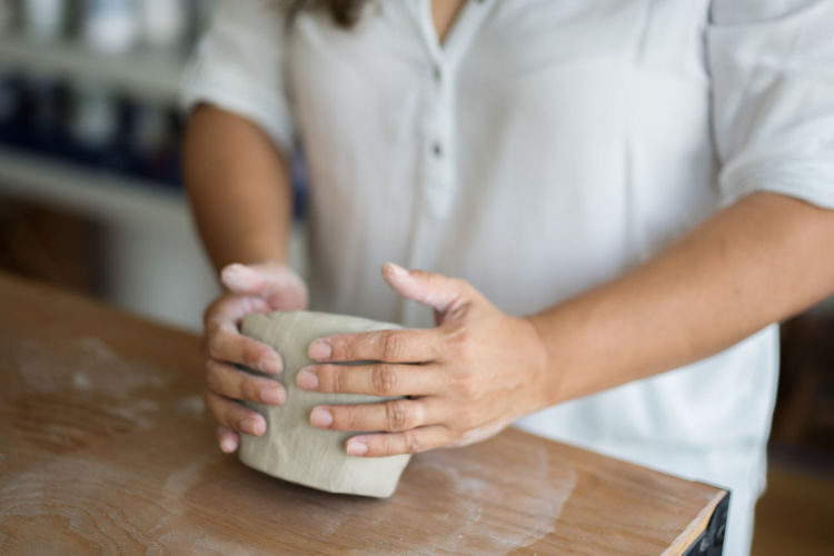 Midsection of woman kneading clay on table in workshop
