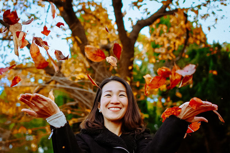 One Person Portrait Smiling Autumn Front View Young Adult Tree Looking At Camera Happiness Long Hair Leisure Activity Real People Young Women Plant Part Lifestyles Focus On Foreground Leaf Plant Headshot Hairstyle Hair Change Outdoors Body Part Hand