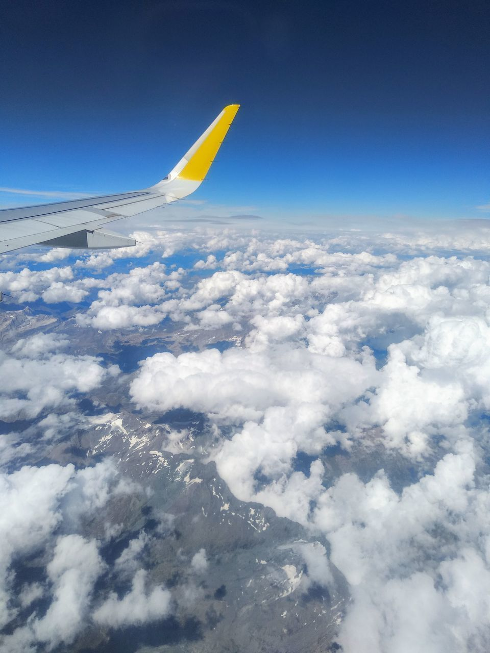 cloud - sky, sky, air vehicle, airplane, flying, aircraft wing, mode of transportation, no people, beauty in nature, transportation, nature, cloudscape, scenics - nature, blue, travel, mid-air, aerial view, day, outdoors, sunlight, softness, above, meteorology