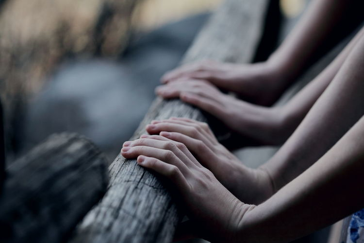 Cropped image of hands touching wooden railing