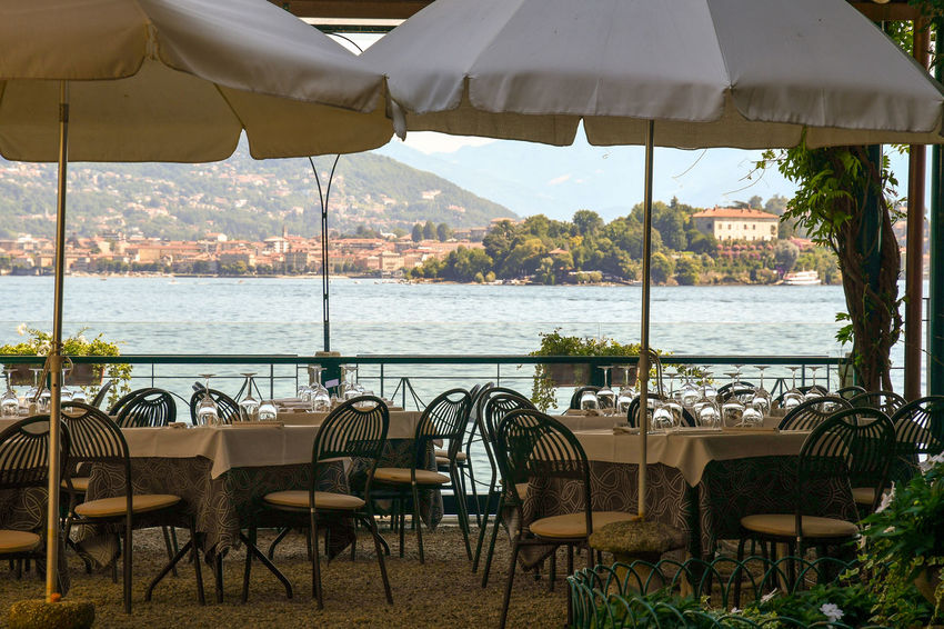 Outdoor restaurant with a view of the Maggiore Lake, Piedmont, Italy Seat Water Restaurant Cafe No People Absence Nature Day Parasol Empty Furniture Sunlight Land Outdoors Setting Lake Tourism Al Fresco Maggiore Lake Isola Madre Piedmont Italy Isola Dei Pescatori Travel Chairs And Tables Vacation