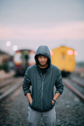 Portrait of man wearing hooded jacket while standing against trains at railroad tracks