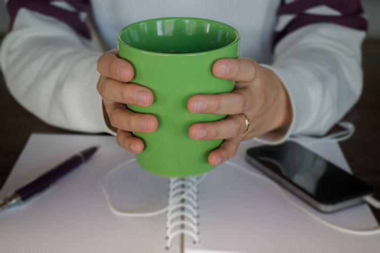 Midsection of woman holding mug
