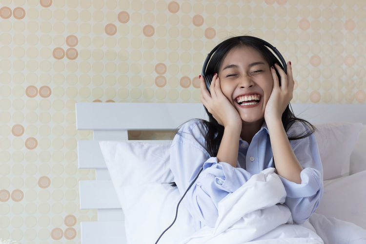 Happy Young Woman Listening To Music On Bed At Home