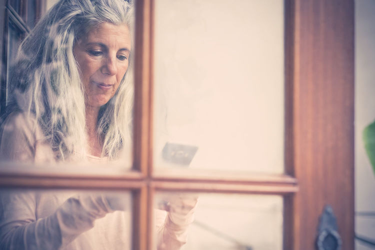 Woman holding phone by window