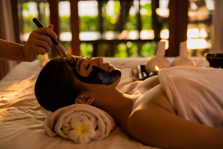 Cropped hand applying facial mask to young woman lying on bed in spa
