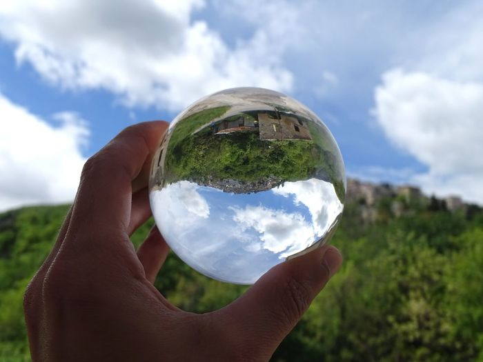 Cropped image of hand holding crystal ball against sky