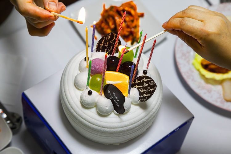 Cropped Image Of Hands Lighting Candles On Cake