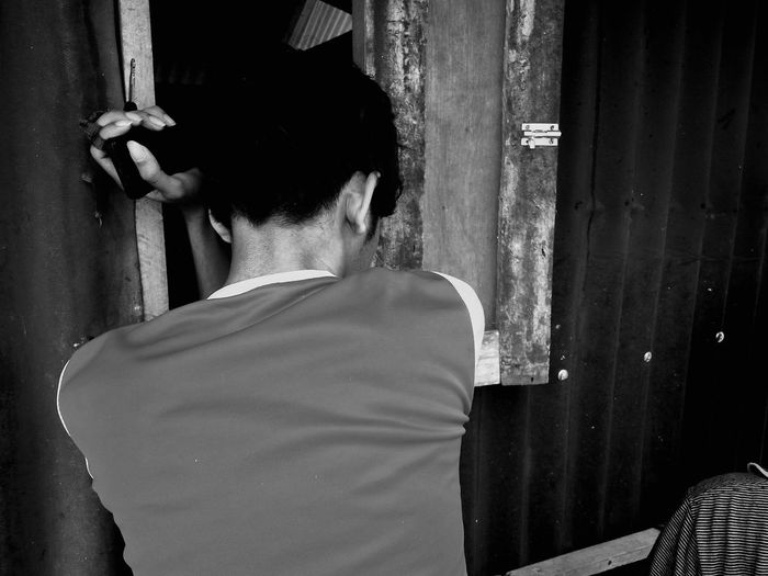 Rear view of man leaning on corrugated wall by window