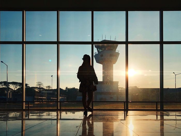 Silhouette man standing at airport against sky during sunset