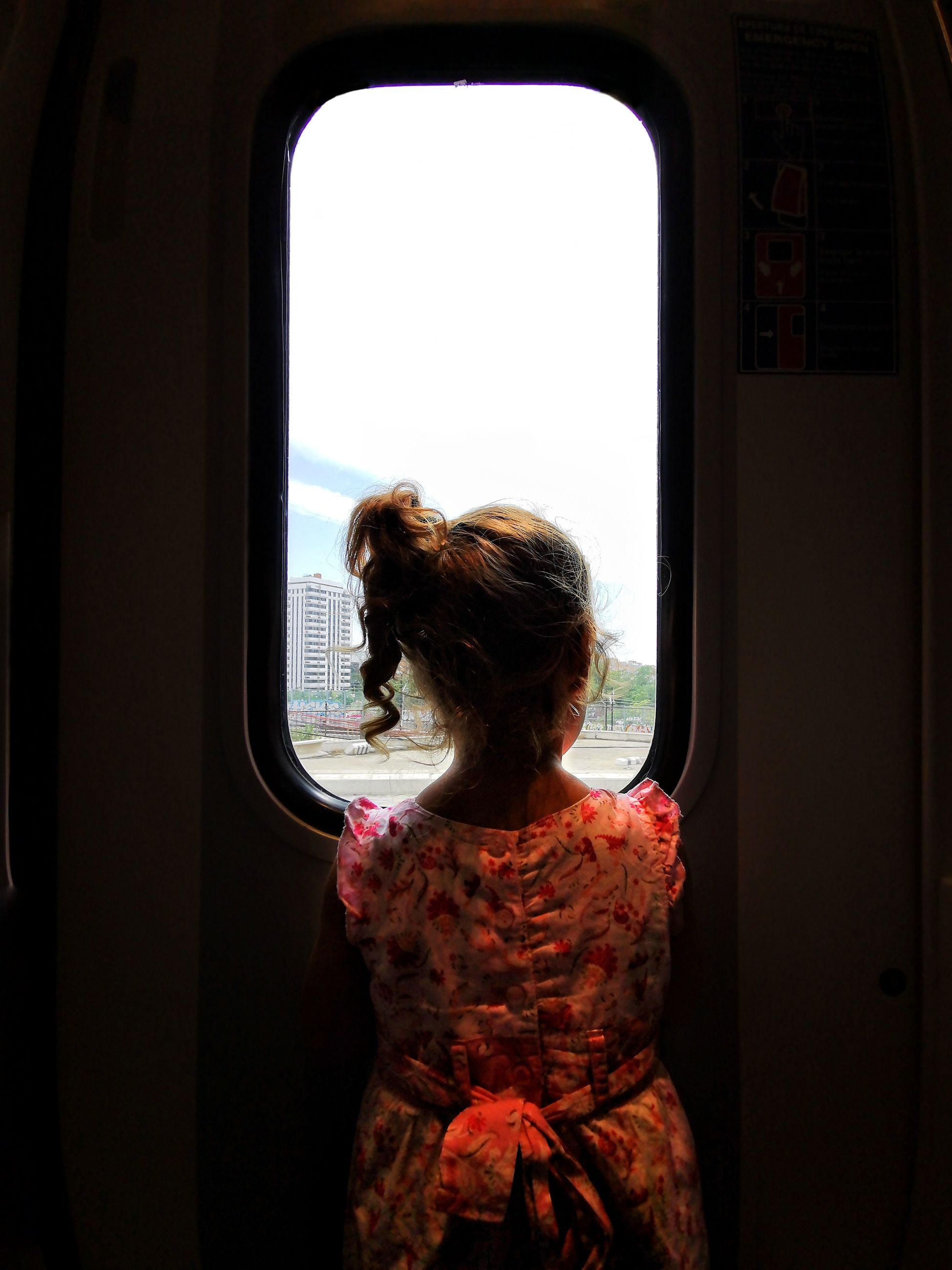 vehicle interior, one person, window, mode of transportation, transportation, real people, lifestyles, transparent, travel, women, rear view, public transportation, looking through window, train, journey, adult, glass - material, rail transportation, day, outdoors, hairstyle