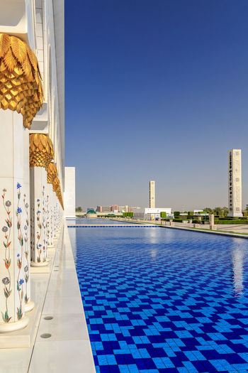 Outside the Grand Mosque in Abu Dhabi Pool Architecture Water Blue Built Structure Clear Sky Building Building Exterior No People Copy Space Outdoors Tiled Floor Tile Luxury Poolside Mosque Grand Mosque Grand Mosque Abu Dhabi Travel Travel Destinations Gold Gold Colored