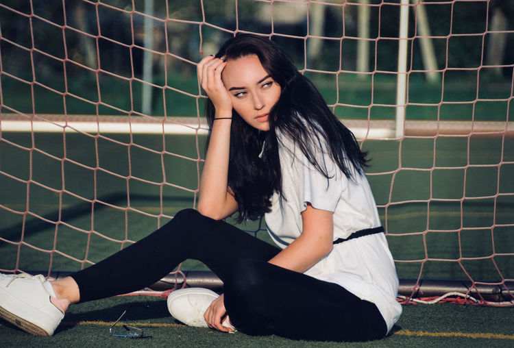 Side view of young woman looking away while sitting by net