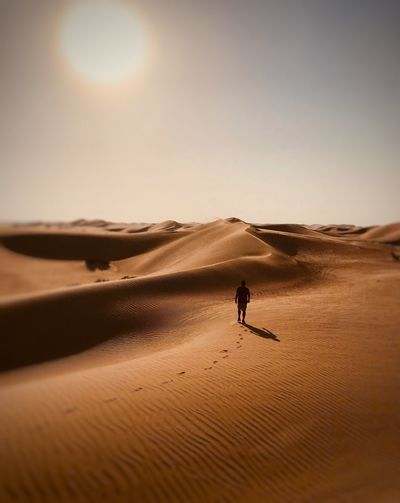 Rear view of silhouette man walking at desert against sky during sunny day