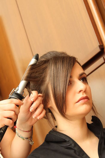 Cropped hands of hairdresser curling woman hair