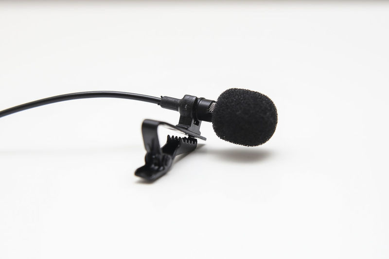 Close up of lapel microphone in an isolated background Audio Electronic Isolated Mic Sound Tiny Acessory Clip Close-up Compact Devices Lapel Media Microphone Microphone Stand Small Technology Top View White Background