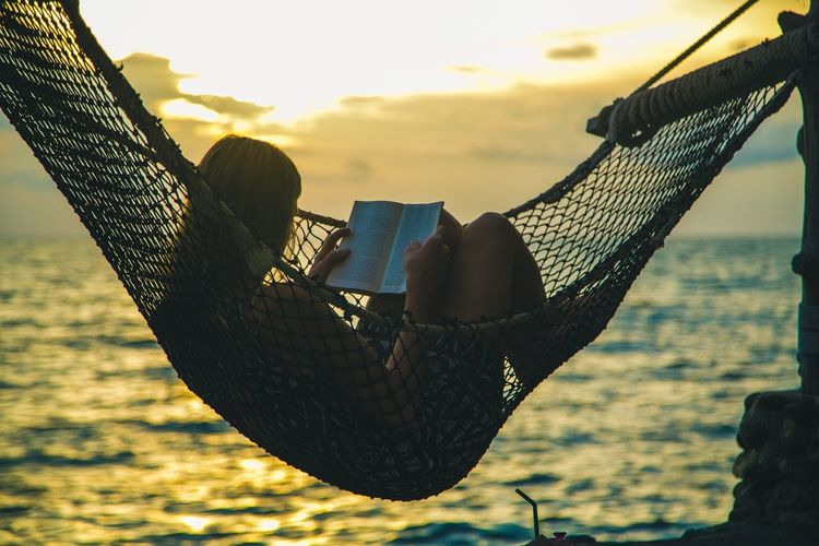 Woman reading book while resting in hammock at beach