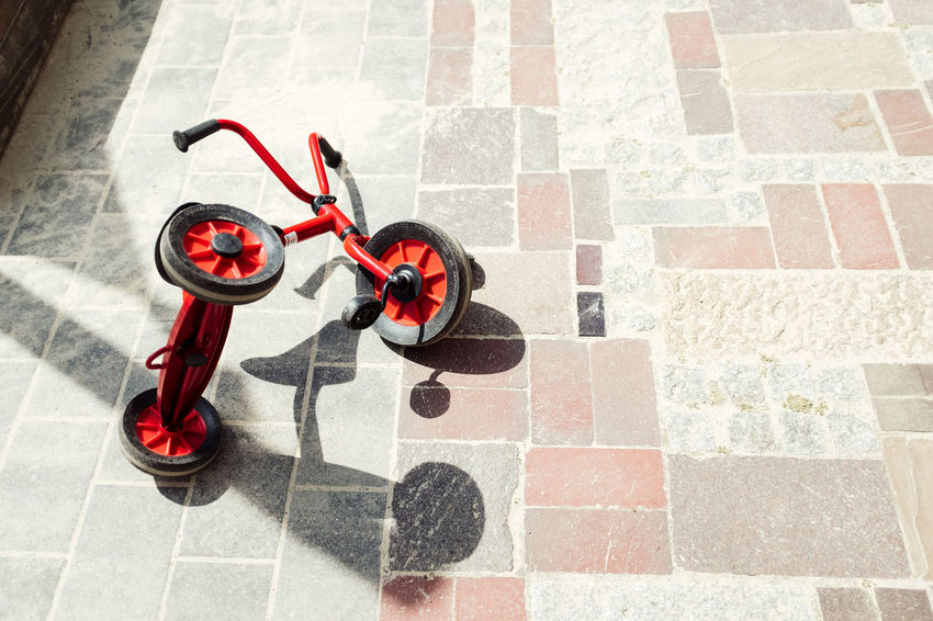 TRICYCLE Famous Toys Absence Day Flooring High Angle View Nature No People Outdoors Pattern Paving Stone Plastic Red Shadow Single Object Stone Sunlight Tile Tiled Floor Toy Tricycle Water The Still Life Photographer - 2018 EyeEm Awards