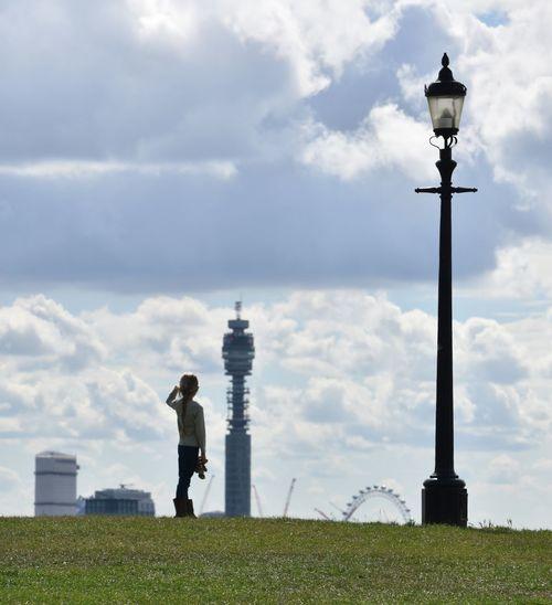 Man standing by street light on field against sky