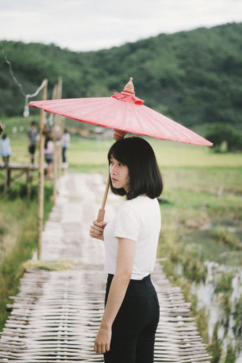 Portrait of smiling woman with umbrella standing on boardwalk