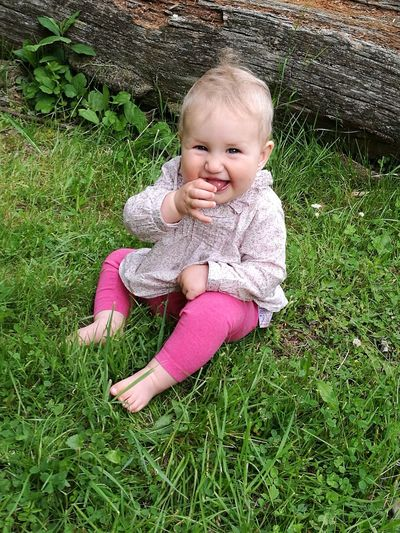 Portrait Of Smiling Girl Sitting On Grass