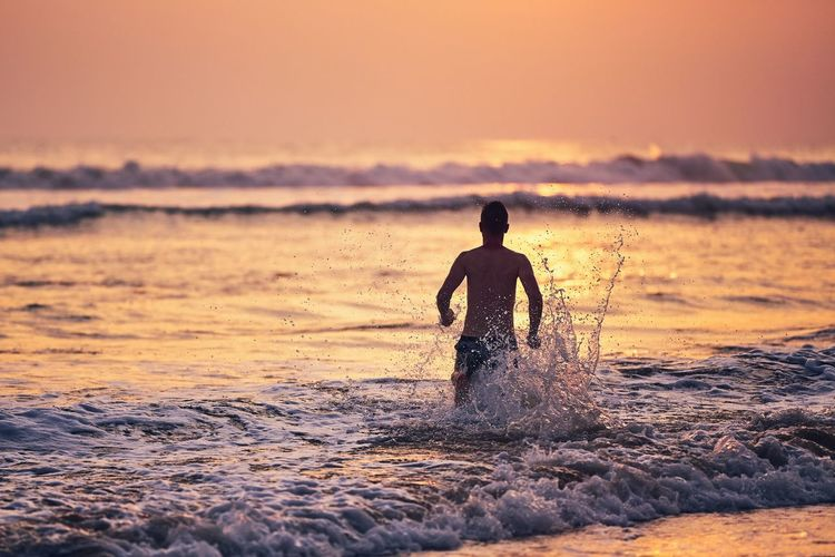 Vacations on the beach. Happy young man running to the sea at the sunset. Sky Beach Running Sea Water Splashing Fun Enjoyment Happiness Sunset One Person Wave Beauty In Nature Lifestyles Nature Men Motion Horizon Over Water Real People Summer Vacations Refreshment Activity Moody Sky Joy