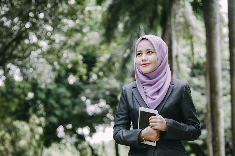 Businesswoman in hijab holding digital tablet against trees
