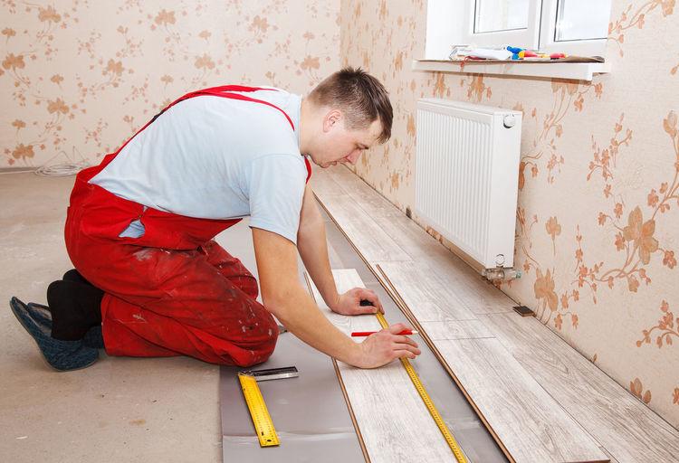 Man Measuring Hardwood Floor Panels In Home
