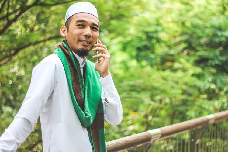 Smiling Man In Traditional Clothing Talking On Mobile Phone Standing Against Trees