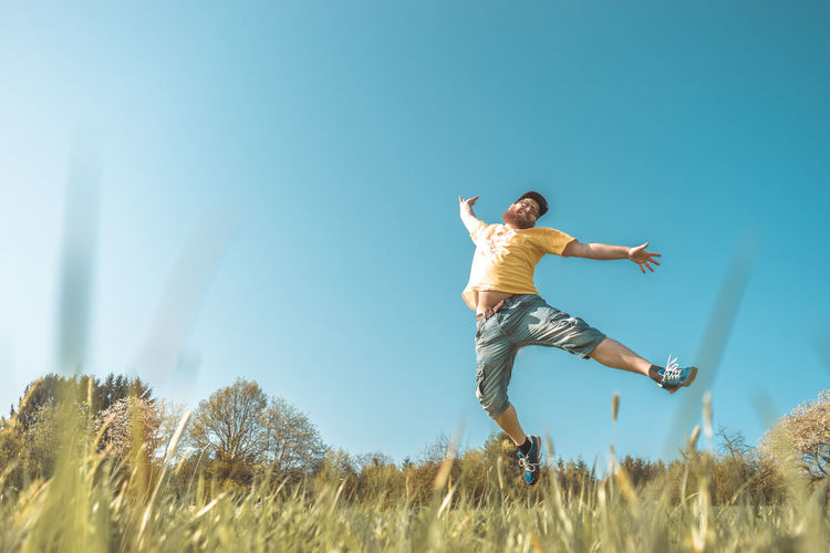 Arms Outstretched Arms Raised Casual Clothing Clear Sky Day Enjoyment Field Full Length Grass Human Arm Jumping Land Leisure Activity Lifestyles Limb Men Nature One Person Outdoors Plant Real People Sky Springtime Yellow Young Adult