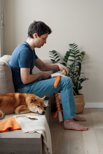 Adult man making diy homemade educational toys for dogs using a tutorial from the internet