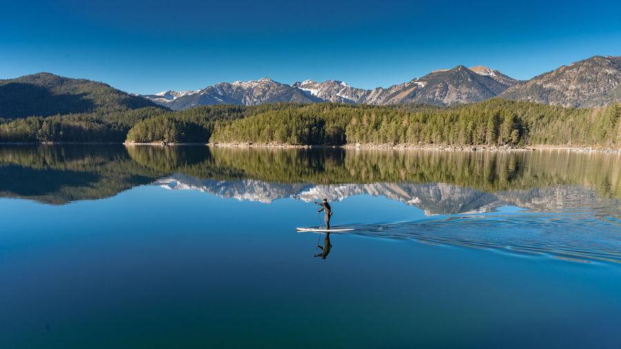 Person paddleboarding on lake