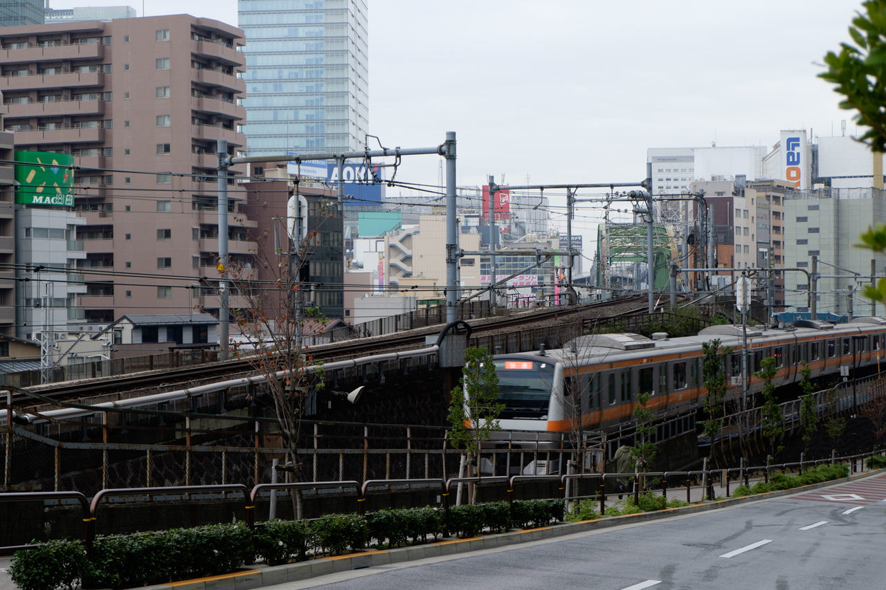 Train Moving By Buildings In City