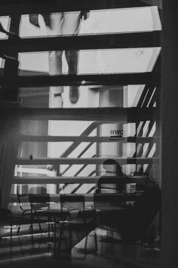 Black Reflection White Refraction One Person Real People Indoors  Seat Sitting Architecture Table Window Built Structure Chair Business Education Lifestyles Book Reflection Staircase Publication Men Stack Black And White Black & White Indoors