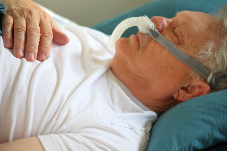 Sleeping senior man with CPAP attachment Healthcare And Medicine Real People Lying Down Indoors  Close-up Sleeping CPAP Machine Continuous Positive Airway Breathing Treatment Senior Adult Napping Profile Tubing In Bed Pillow Hand Fingers Attachment Device Resting Medical Equipment Sleep Apnea Condition
