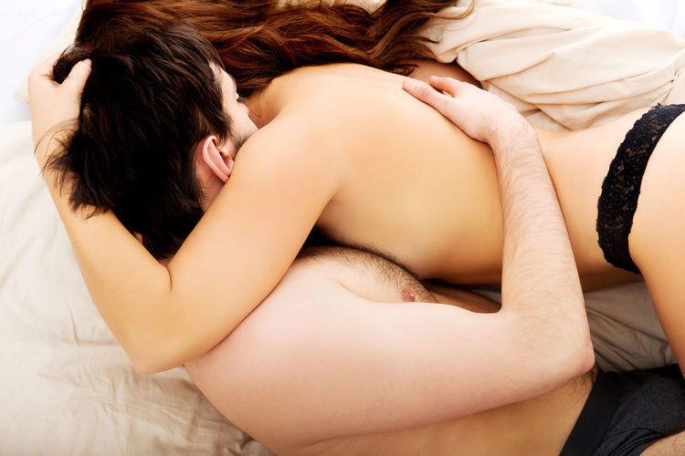 Young Couple Embracing On Bed At Home