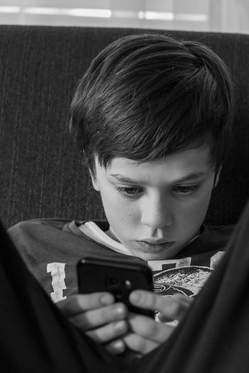 Portrait of boy using mobile phone at home