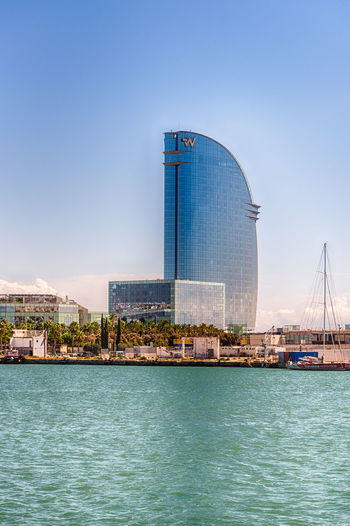 BARCELONA - AUGUST 10: W Barcelona hotel, aka Hotel Vela, designed by Loredana Gengler and located in the Barceloneta district, waterfront of Barcelona, Catalonia, Spain, as seen on August 10, 2017 Architecture Building Exterior Built Structure Water Sky City Building Waterfront Transportation Nature No People Sea Day Nautical Vessel Travel Destinations Blue Travel Outdoors Modern Cityscape Skyscraper