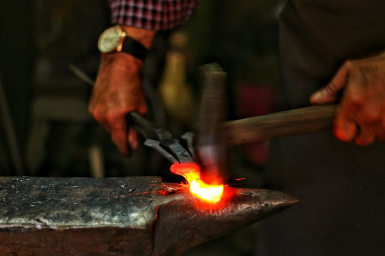 Midsection of blacksmith working at workshop