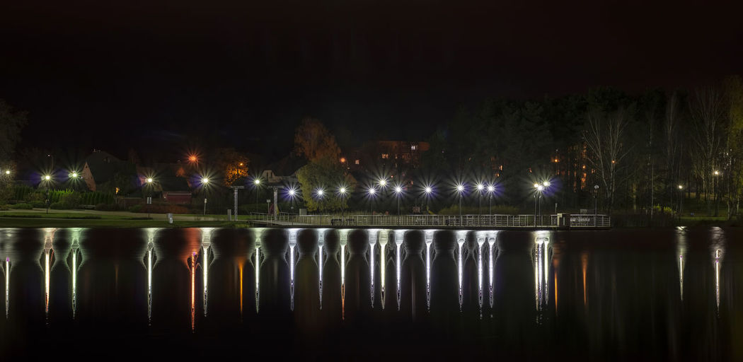 Reflection Of Illuminated Trees In Lake At Night