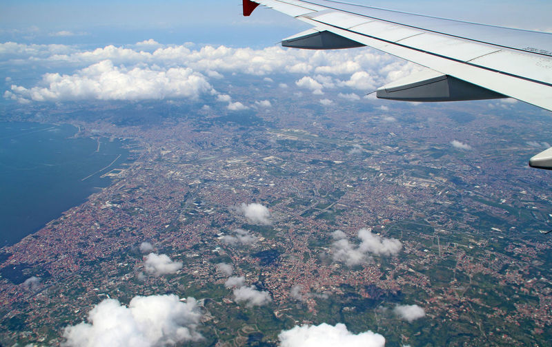 Aerial view of aircraft wing over landscape against sky