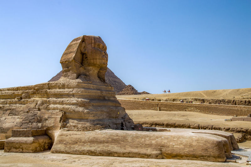 The sphinx statue in desert against clear blue sky