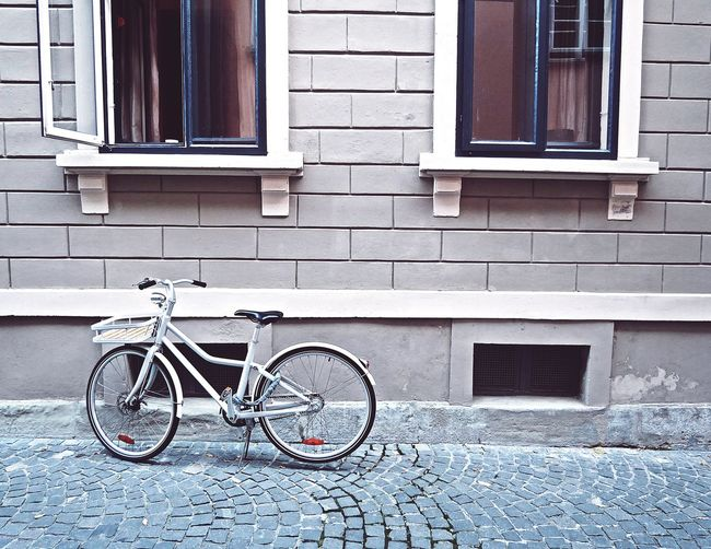 Bicycle parked on street against building